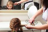 Hairdresser straightening hair little girl child in hairdressing beauty salon — Stock Photo