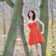 Full length fashionable woman in vibrant red dress in park — Stock Photo