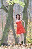 Full length fashionable woman in vibrant red dress in park — Foto Stock