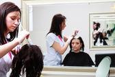 Hairdresser applying color female customer at salon, doing hair dye — Stock Photo