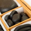 Black spa zen massage stones in wooden case blank copy space — Stock Photo #36537103