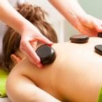 Spa salon. Woman relaxing having hot stone massage. Bodycare. — Stock Photo