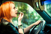 Woman driver painting her lips while driving a car — Stock Photo