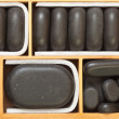 Black spa zen massage stones in wooden case as background — Stock Photo