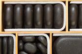 Black spa zen massage stones in wooden case as background — Stok fotoğraf