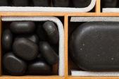 Black spa zen massage stones in wooden case as background — Foto de Stock