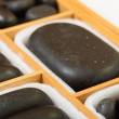 Black spa zen massage stones in wooden case blank copy space — Stock Photo #36691155