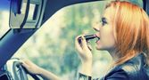 Red haired woman applying lipstick on lips in car. Danger on road. — Stock Photo