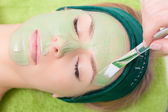 Beauty salon. Cosmetician applying facial mask at woman face. — Stock Photo