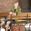 Stock Photo: Young handsome man with suitcase waits on bench