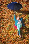 Young girl relaxing with umbrella in autumnal park — Foto de Stock