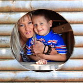 Mother and son peeks through hole at playground — Stock Photo