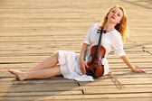 The blonde girl with a violin outdoor — Stok fotoğraf