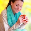 Stock Photo: Happy girl relaxing in the autumn park enjoying hot drink