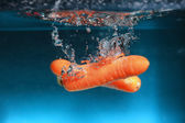 Carrot in the water splash over blue — Stockfoto