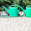 Watering green can and hose in garden — Stock Photo