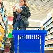 Woman shopping with blue basket at supermarket shop. Retail. — Stock Photo #37203085