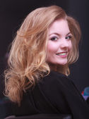 Beautiful smiling girl with blond wavy hair by hairdresser in beauty salon — Stock Photo