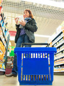 Woman shopping with blue basket at supermarket shop. Retail. — Stockfoto