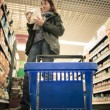 Woman shopping with blue basket at supermarket — Stock Photo #37258411