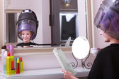 Girl reading magazine drinking coffee. Hairdryer in hair beauty salon — Stock Photo
