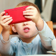 Boy taking photo with red mobile phone — Stock Photo