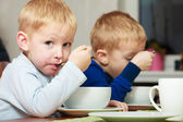 Boys kids children eating corn flakes breakfast meal at the table — Stock Photo