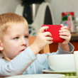 Funny dirty boy child kid taking photo with red mobile phone indoor — Stock Photo