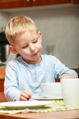Boy kid child eating corn flakes breakfast meal at the table — Foto de Stock
