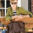 Young handsome man with bag waits on bench — Stock Photo