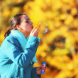 Woman having fun blowing bubbles in autumnal park — Stok fotoğraf