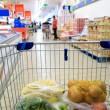 Shopping cart with grocery at supermarket — Stock Photo #37687817