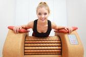 Fille dans l'utilisation de sportwear relax massage matériel sain spa salon — Photo