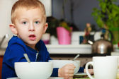 Boy eating corn flakes breakfast meal — Stock Photo