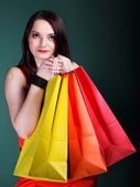 Woman with paper multi coloured shopping bag — Stock Photo