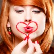 Redhaired girl holding red heart love blowing kiss. Valentines day. — Стоковое фото