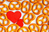 Valentine's day background pretzels pattern and red heart. — Stock Photo