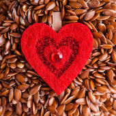 Healthy diet. Flax seeds linseed as food background and red heart — Stock Photo