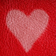 Photo: Valentine's day card. Heart love symbol on red leather background