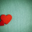 Red wooden decorative hearts on green cloth background. — Stock Photo