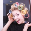 Cheerful funny blond girl hair curlers rollers by haidresser in beauty salon — Stock Photo #39289501