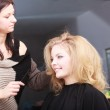 Hairstylist combing female client blond girl in hairdressing salon — Foto de Stock