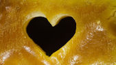 Closeup of golden amber with heart love symbol as background — Stock Photo