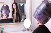 Girl relaxing with hairdryer by hairstylist in hair beauty salon. Mirror. — Stock Photo