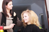 Hairstylist combing female client blond girl in hairdressing salon — Stock Photo