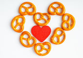 Pretzels and red heart on white background — Stock Photo