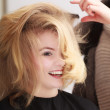 Hairstylist combing female client blond girl in hairdressing salon — Foto Stock