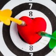 Black white target with two darts in heart love symbol as bullseye — Stock Photo