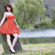 Stock Photo: Full length fashionable woman in vibrant red dress in park