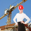 Stock Photo: Female engineer woman in red safety helmet on construction site